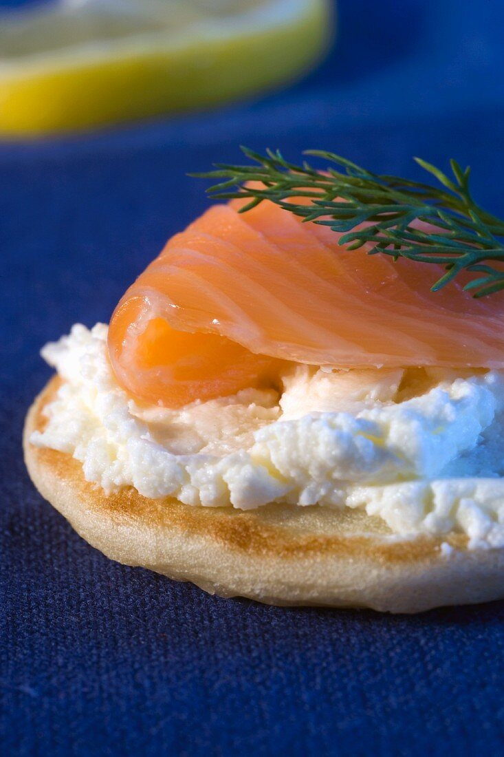 A blini topped with cream cheese, salmon and dill