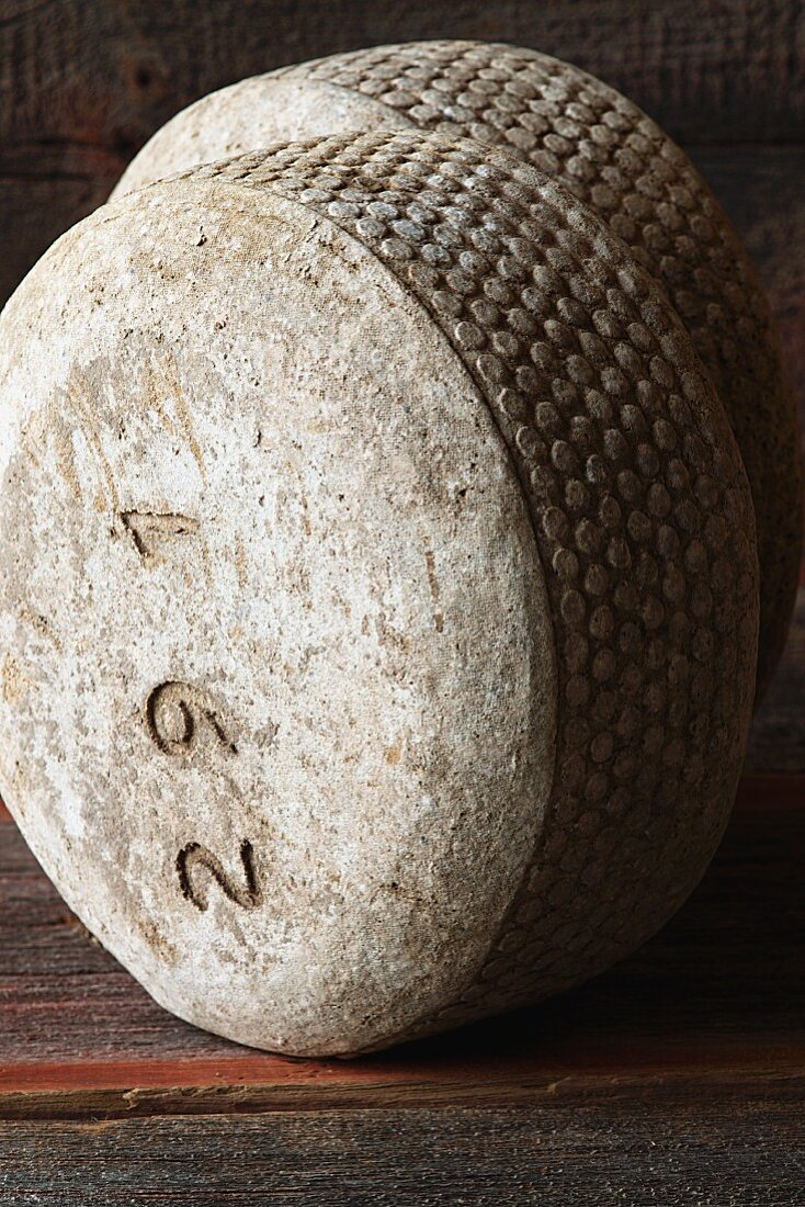 Two Wheels of Sheep Cheese on Wood