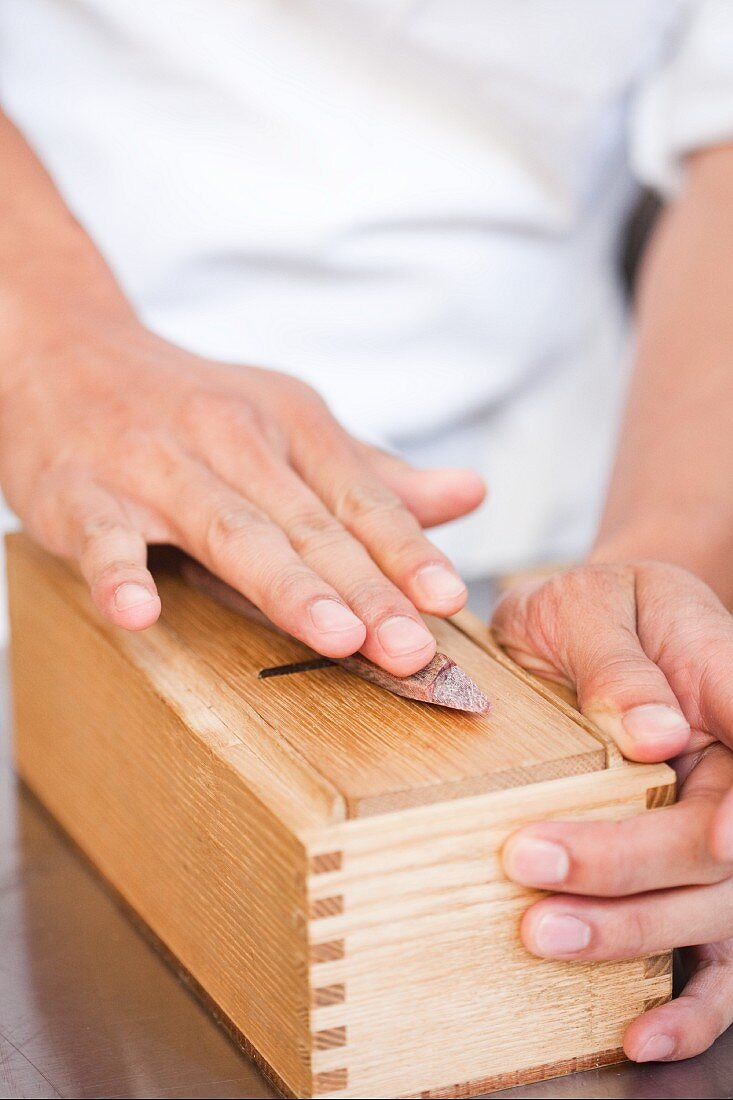 Hand Slicing on a Wooden Box