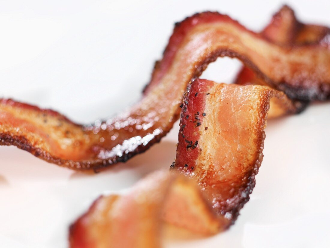 Two Pieces of Crispy Pepper Bacon on White Background; Close Up