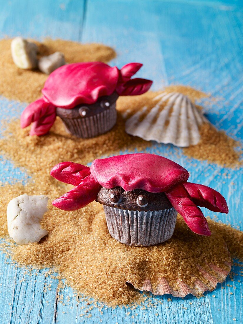 Chocolate muffins shaped like crabs on brown sugar