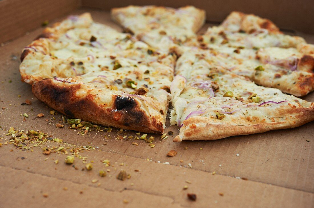 Wood Fired White Pizza with Red Onion, Rosemary, Pistachios and Cheese; Sliced in Box