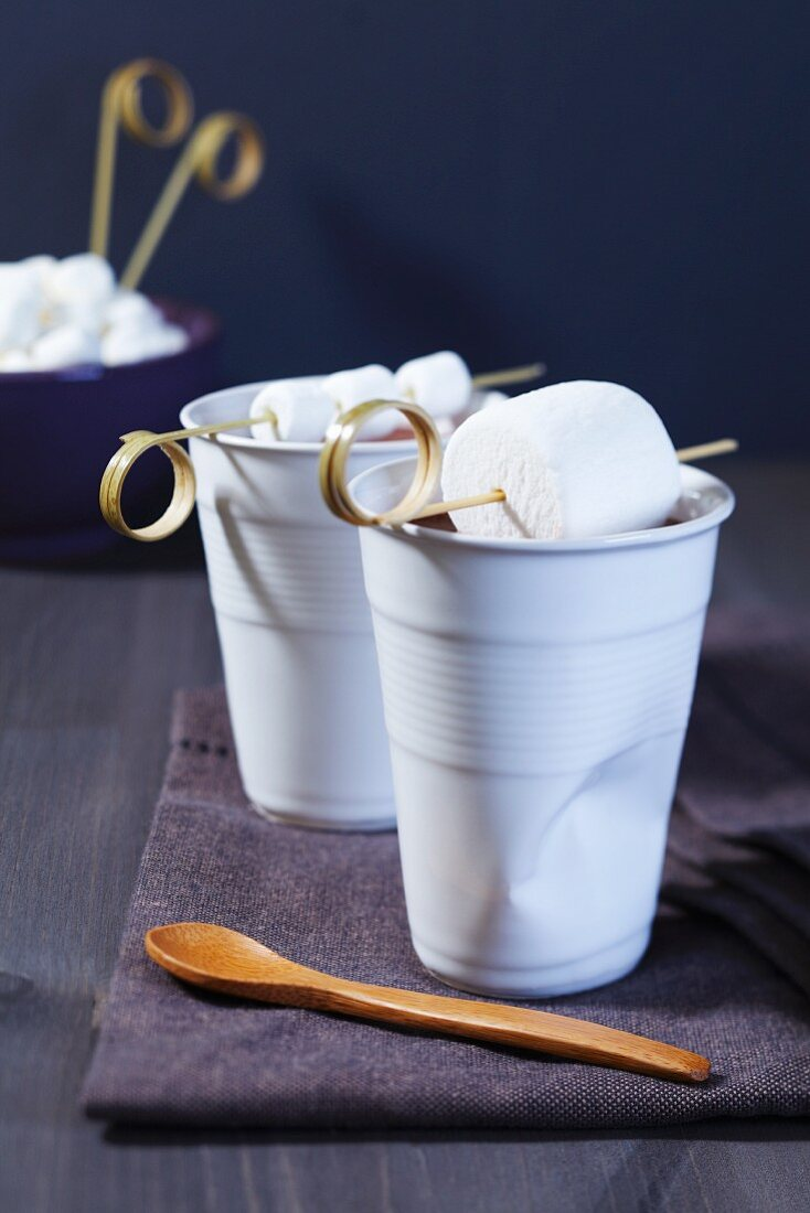 Cups of cocoa with marshmallows on bamboo sticks