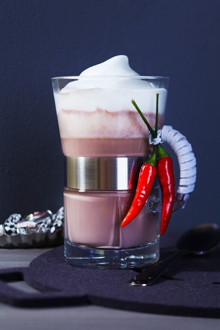A glass of cocoa with chilli peppers and milk foam