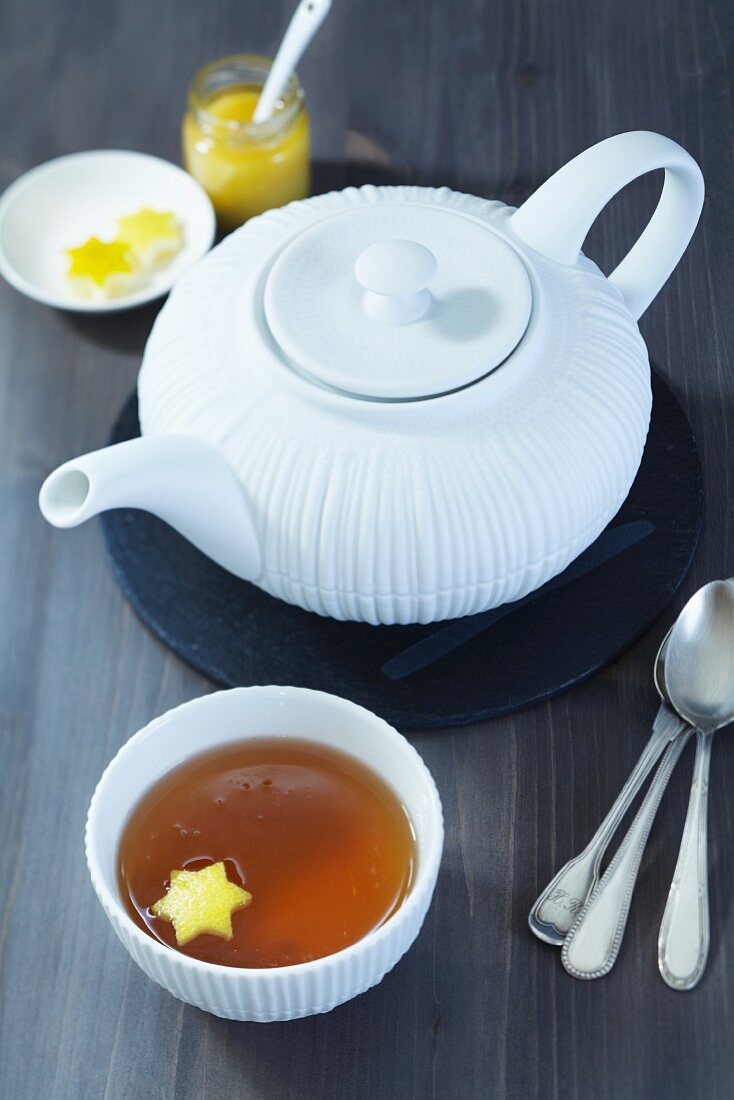 A tea pot, a bowl of tea with a piece of star-shaped lemon zest