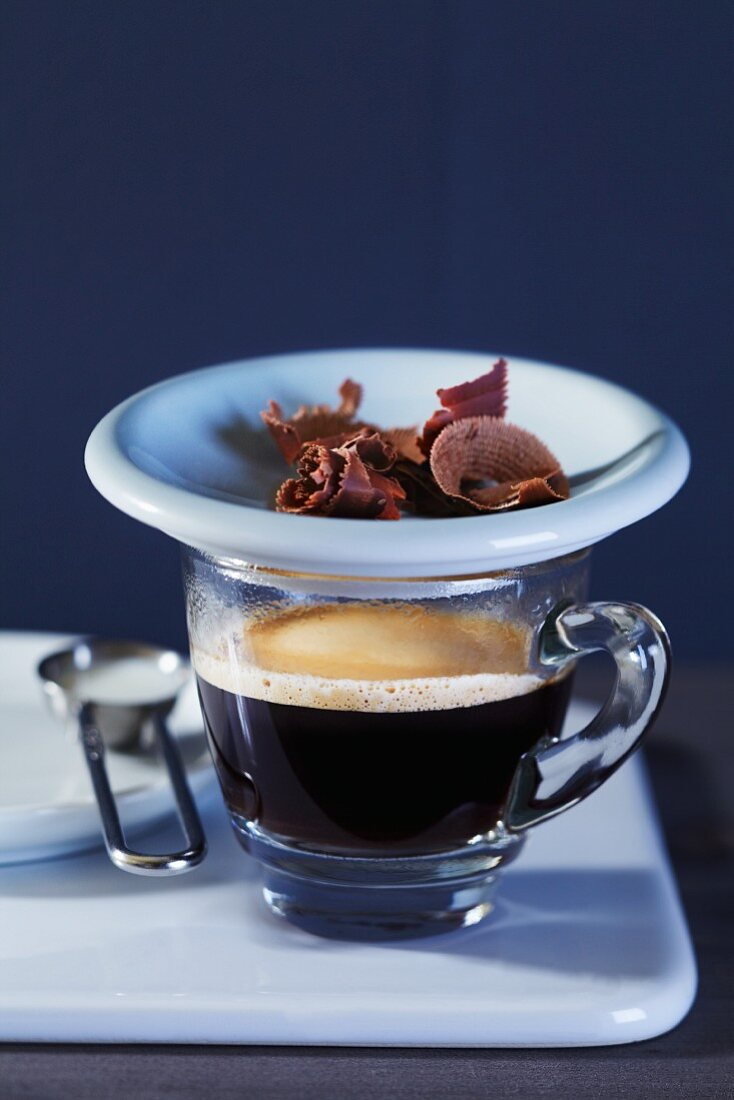 An espresso with a plate of grated chocolate
