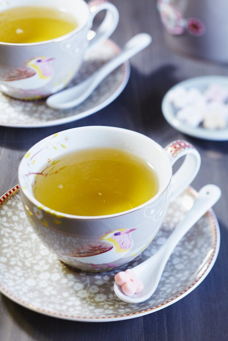 A tea cup with a bird picture and flower-shaped sugar cubes