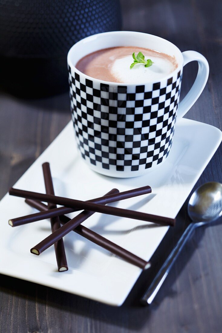 Cocoa with milk foam and mint and chocolate sticks