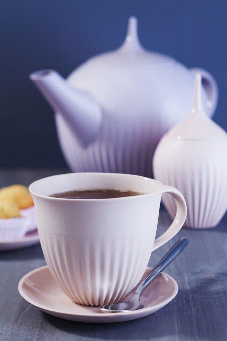 A cup of tea with a tea pot and a sugar pot
