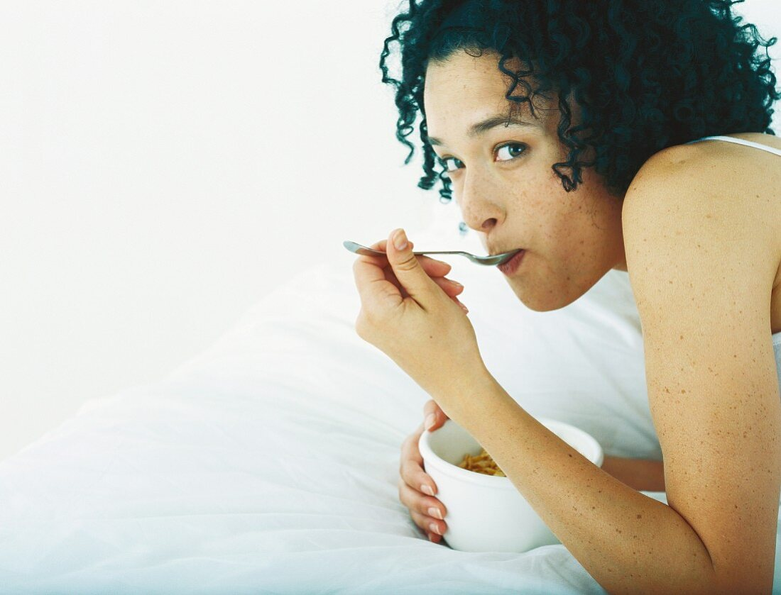 Woman lying on stomach on bed eating from a bowl
