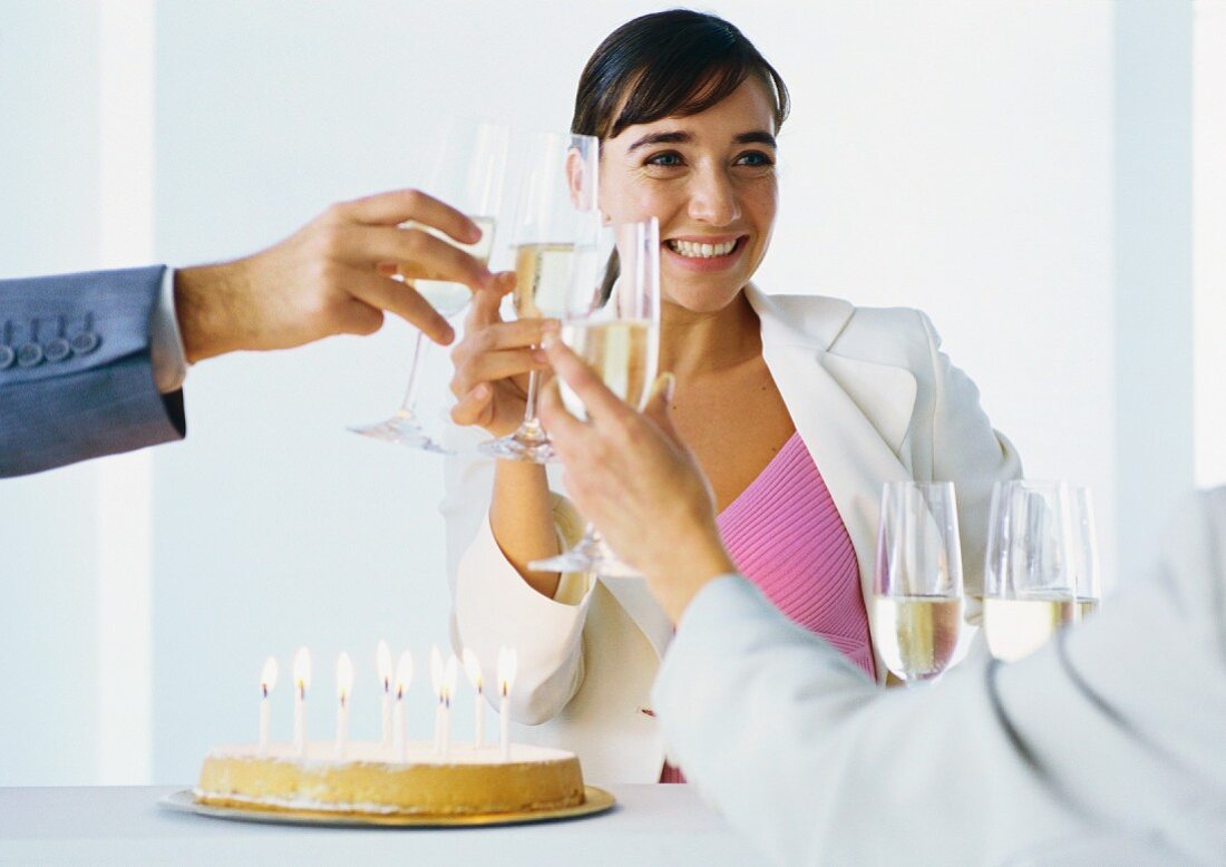 Businesspeople clinking glasses of champagne over birthday cake