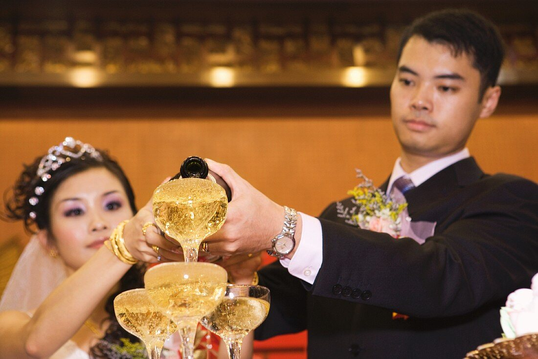 Bride and groom pouring champagne into stacked champagne glasses together