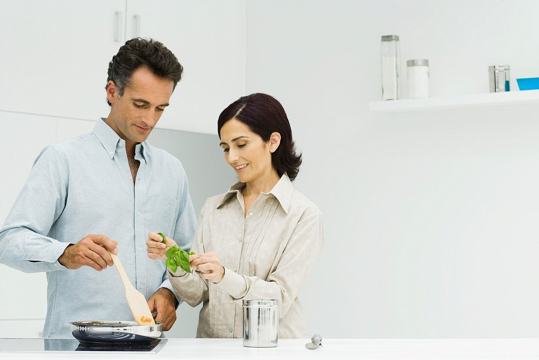 Couple cooking together, woman holding fresh basil