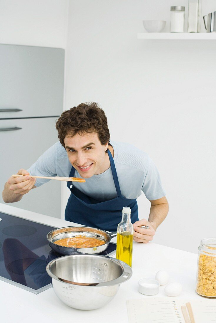 Man cooking in kitchen, bending over to taste sauce, smiling at camera