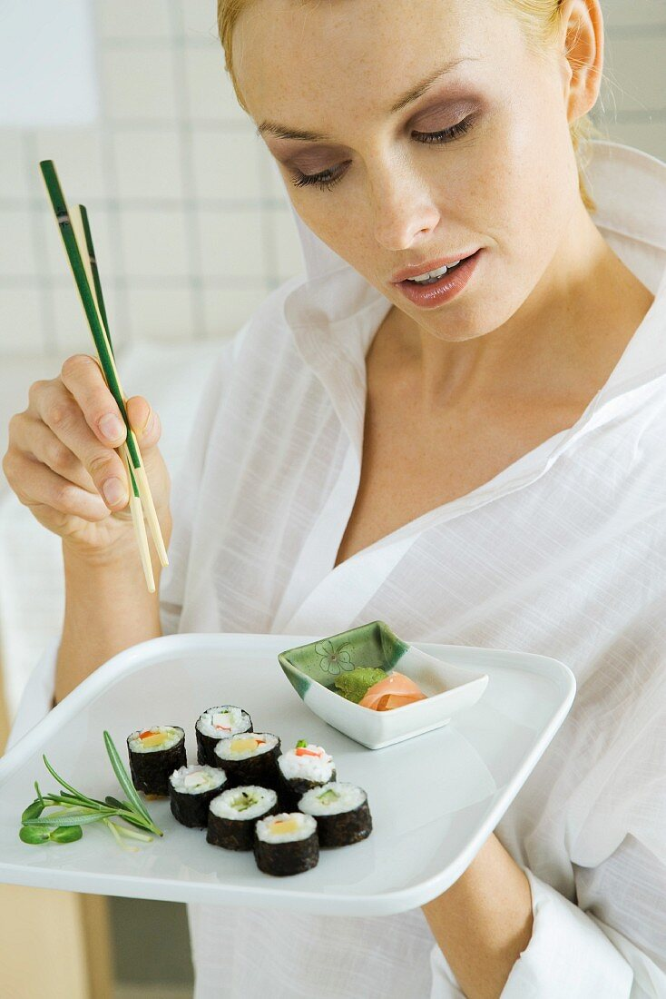 Woman holding maki sushi and chopsticks, looking down