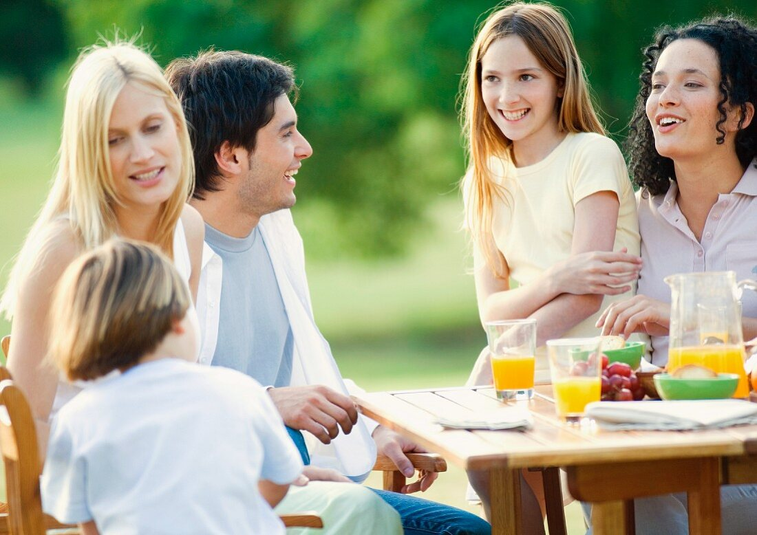 Family and kids sitting around table outdoors