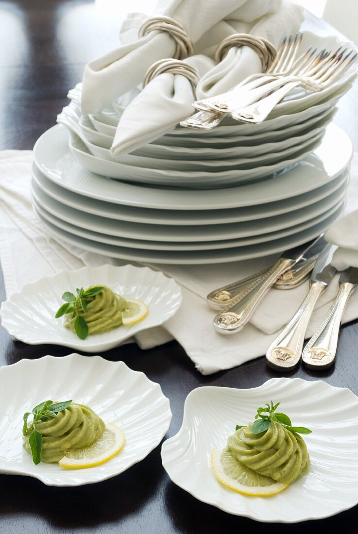 Clamshell-shaped dishes with avocado purée in front of a stack of plates and napkins in silver rings
