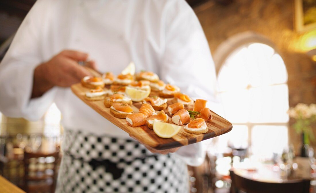 A cook showing a platter of salmon canapes