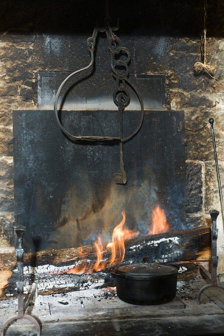 A pot next to an open fire