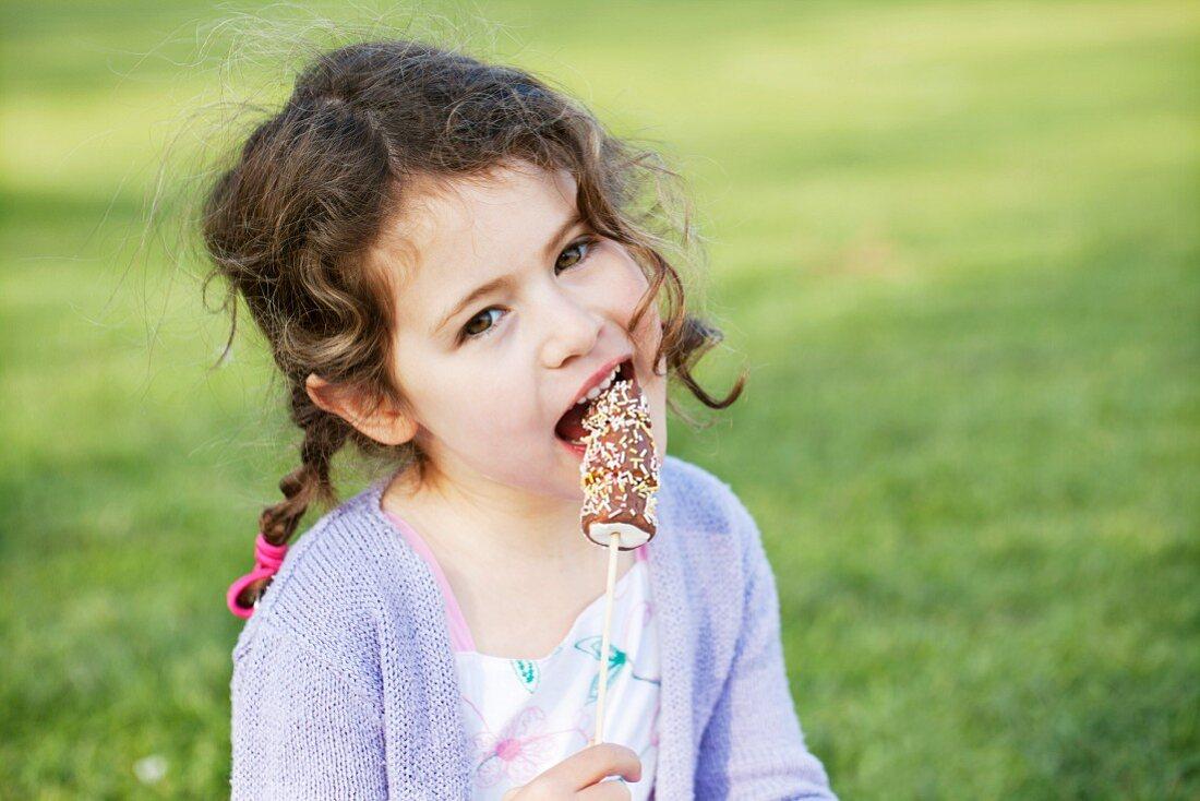 A little girl eating marshmallows