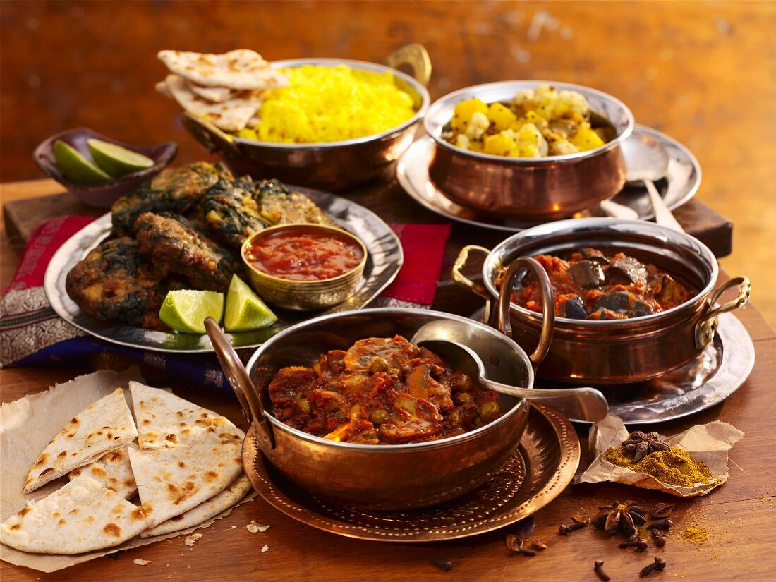 Various Indian dishes with rice and naan bread
