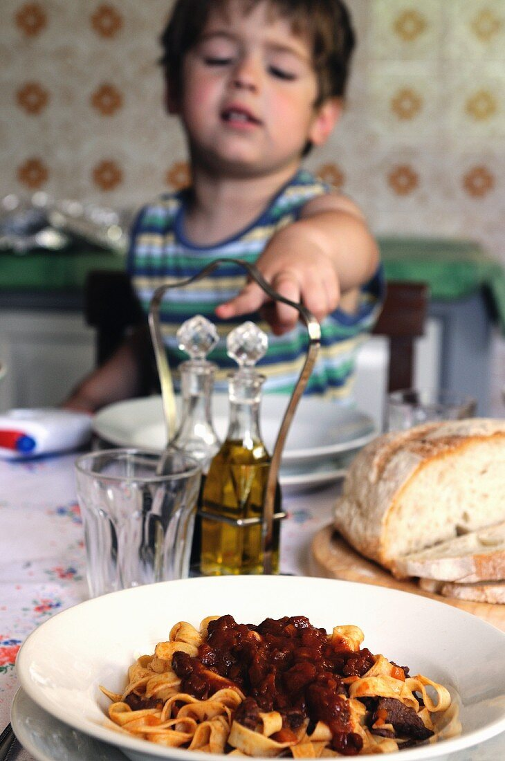A little boy sitting at a table pointing to a plate of tagliatelle