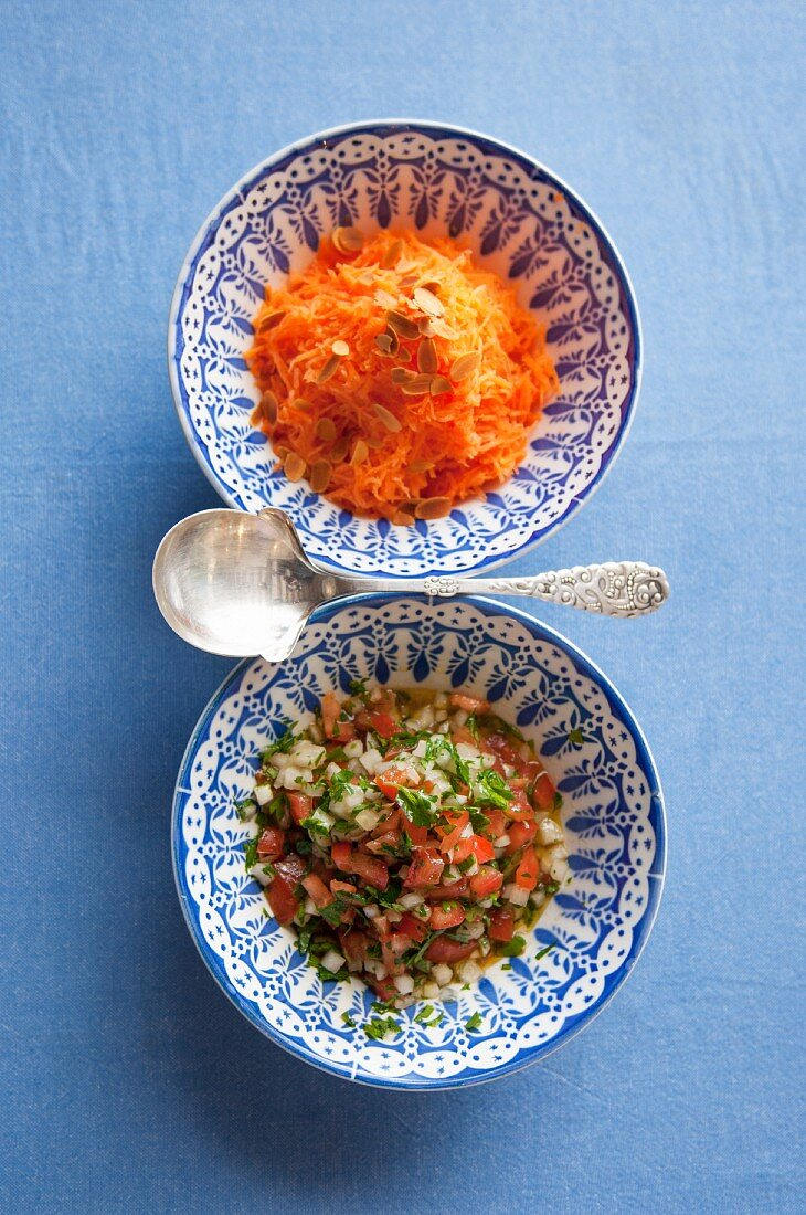 Carrot and orange salad and tomato salad with onion and parsley