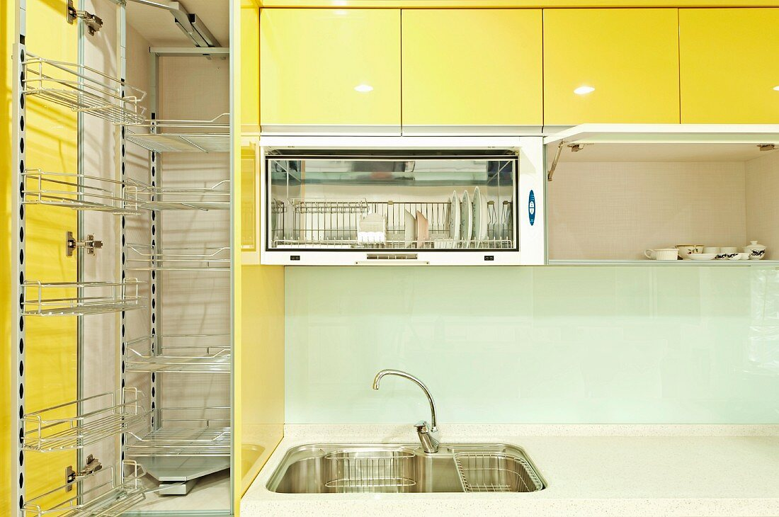 A kitchen cupboard with metal shelves and a sink