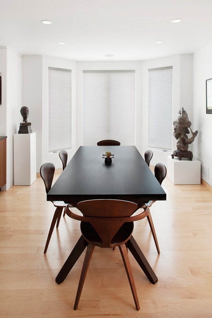A large airy dining room with two sculptures on pedestals in the background