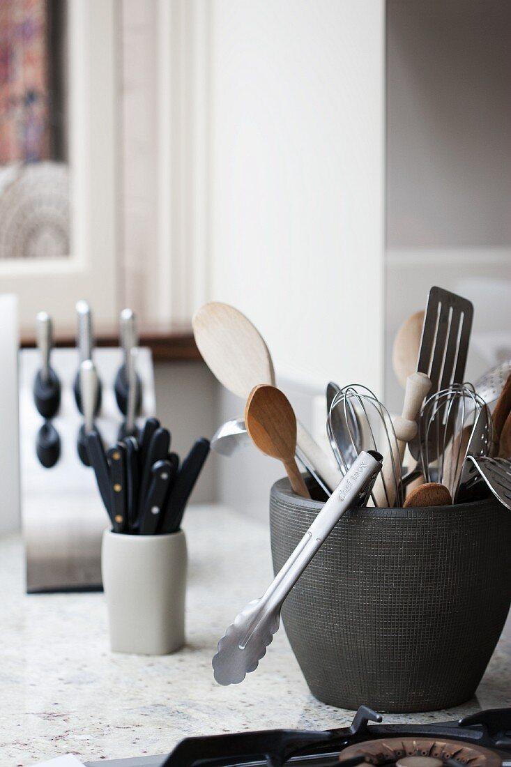 Various kitchen utensils in ceramic pots