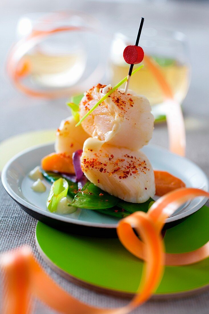A scallop kebab with bay leaves on a bed of vegetables