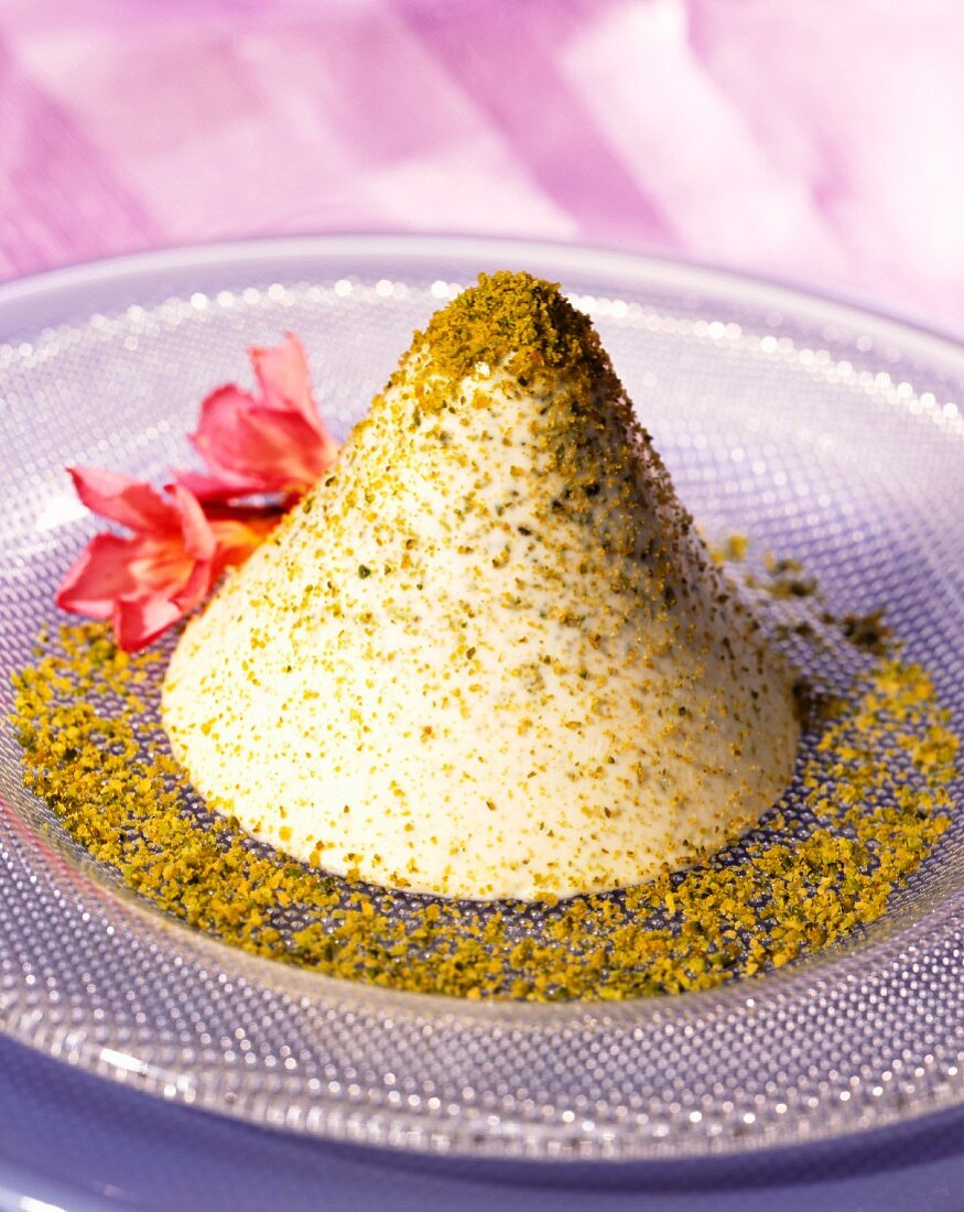 Pistachio cream in a cone shape sprinkled with ground pistachios
