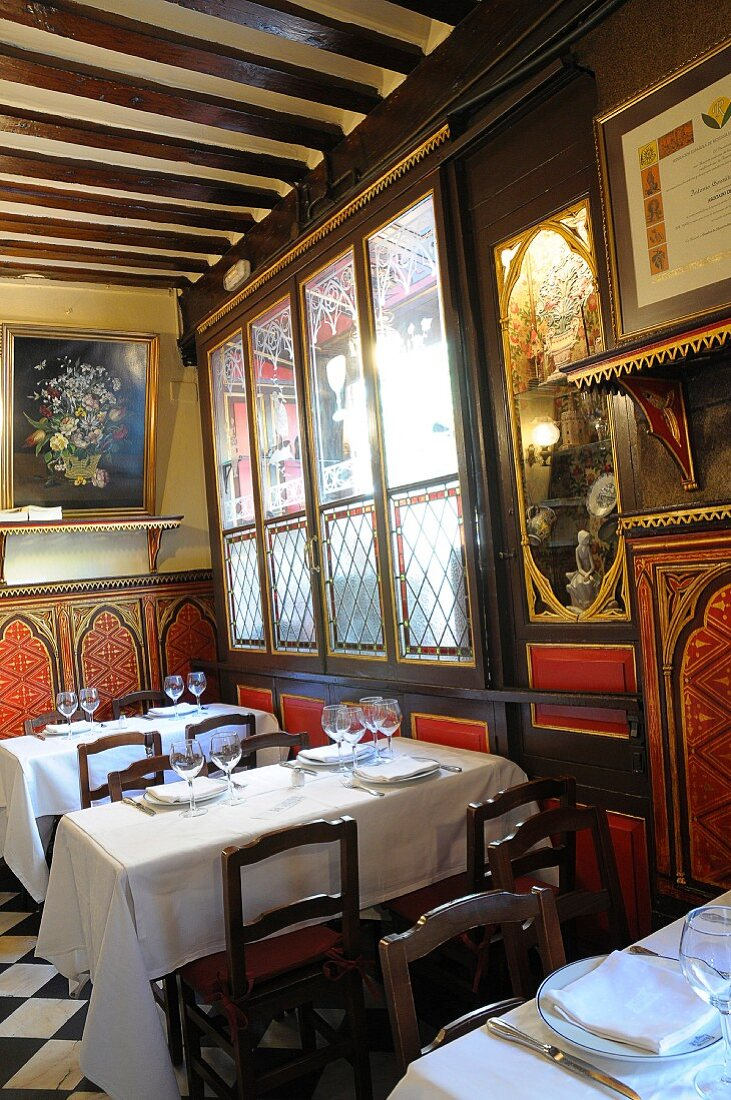Restaurant interior - dining tables set with white tablecloths against antique painted wood panelling and wood-beamed ceiling
