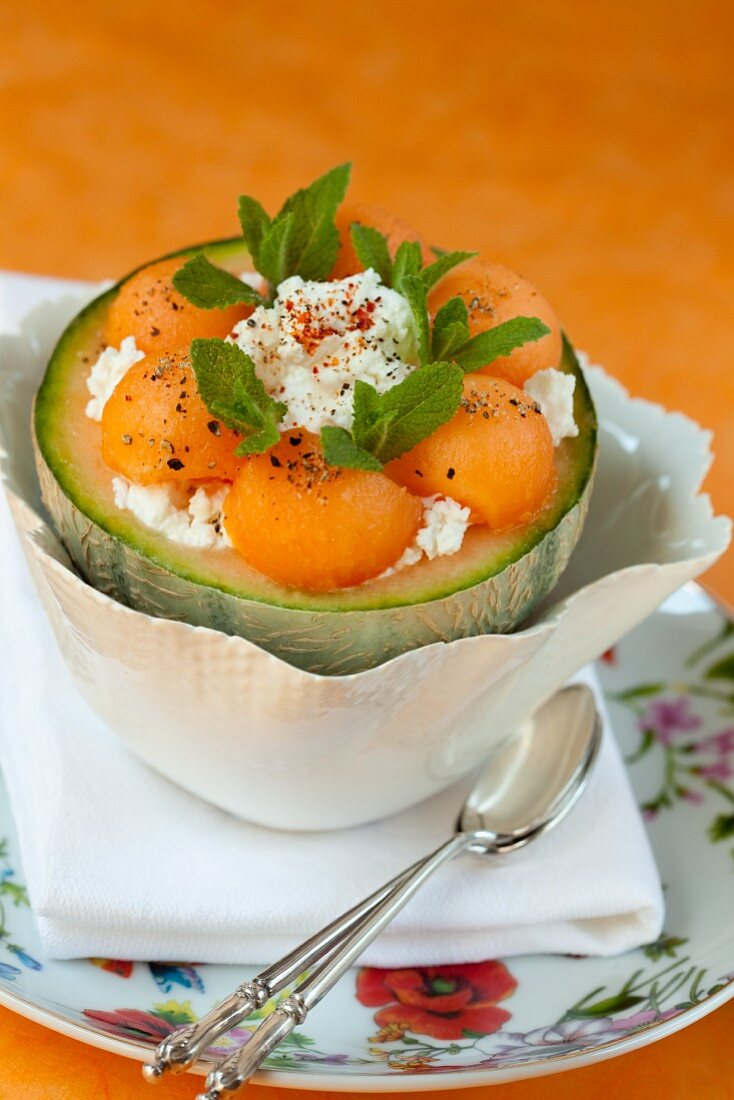 Melon dessert served in a hollowed out melon with cottage cheese and mint