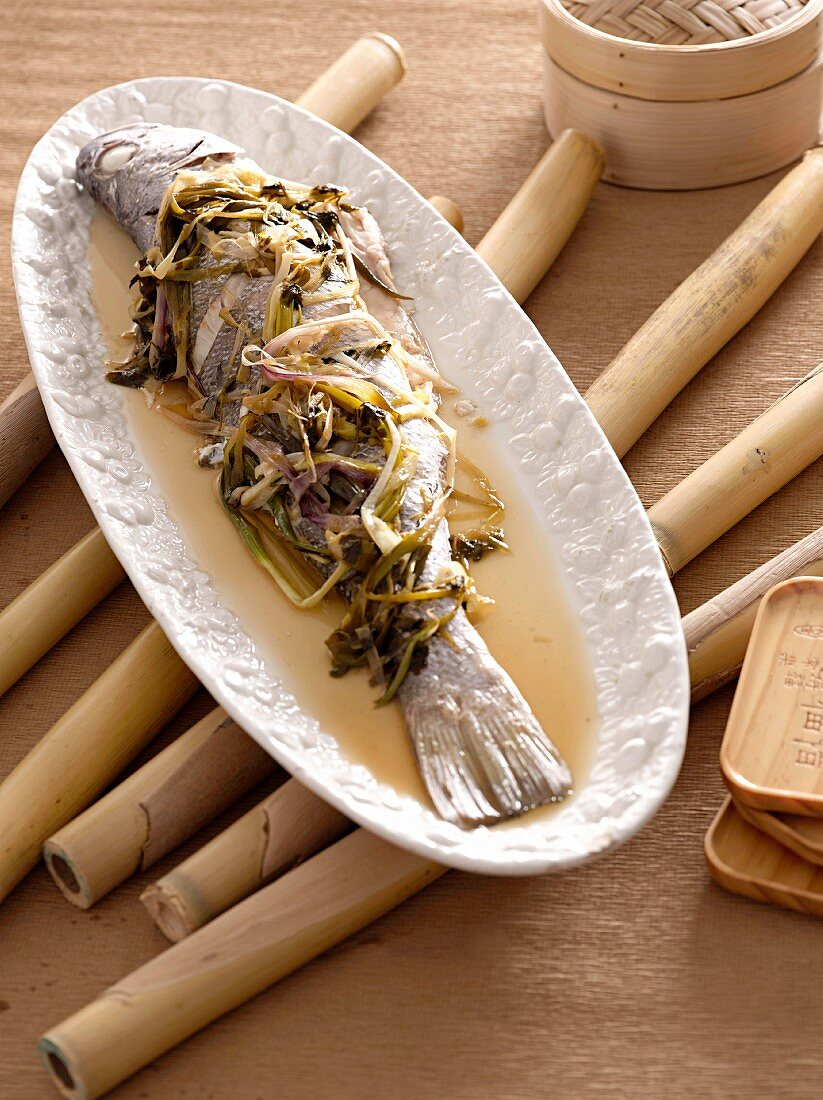 Steamed fish in a beer and ginger sauce with limes