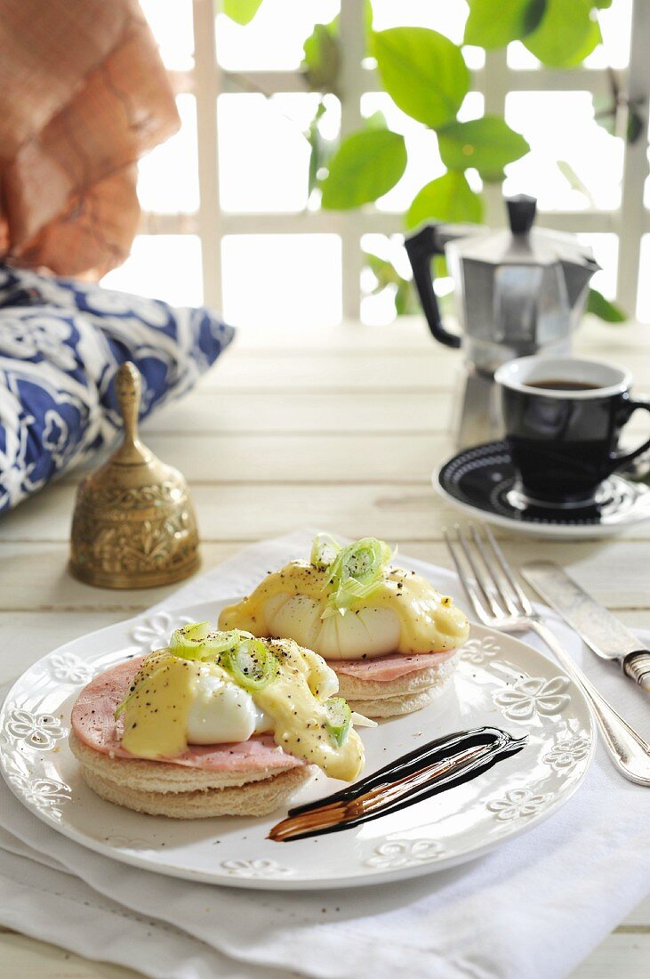 Eggs Benedict: toast topped with ham and poached eggs, with hollandaise sauce