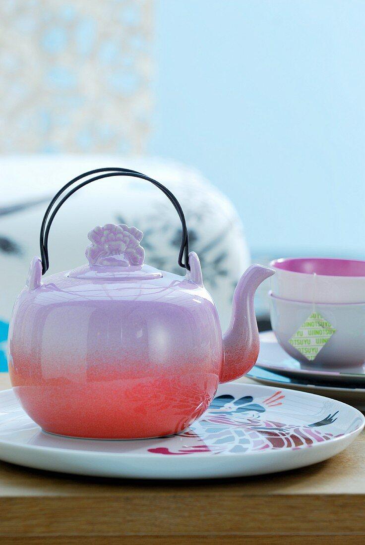 Teegeschirr mit farbiger Teekanne auf Teller stehend vor hellblauem Hintergrund