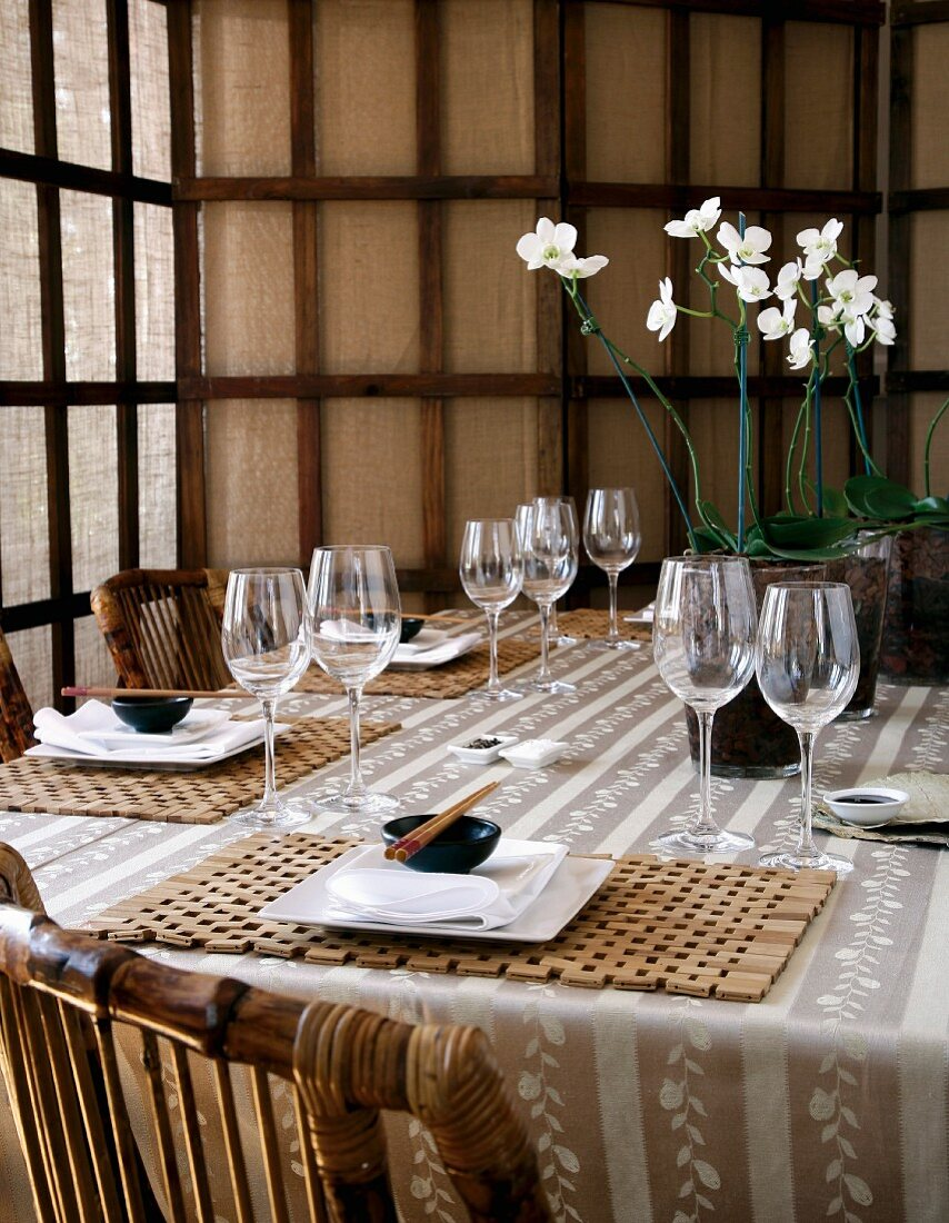 A table laid for an Asian meal, with bamboo wood place mats and white orchids in the centre of the table