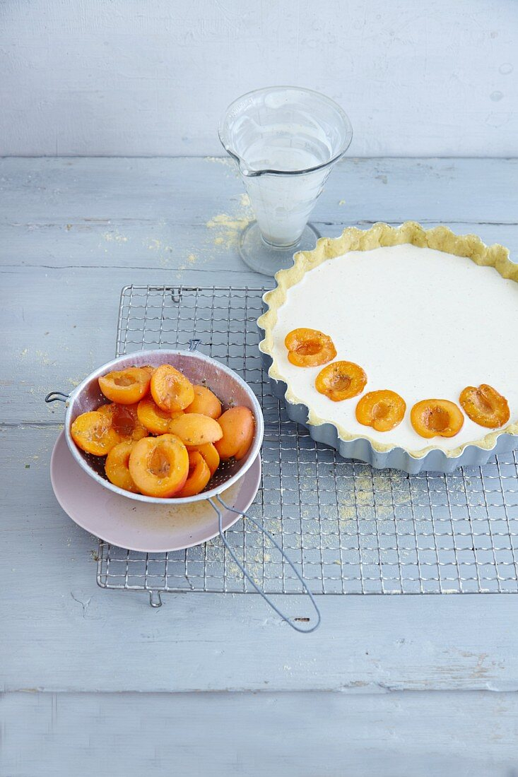 Apricots being placed on a cheese tart topping