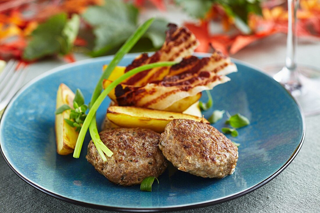 Burgers with potato wedges and crispy bacon