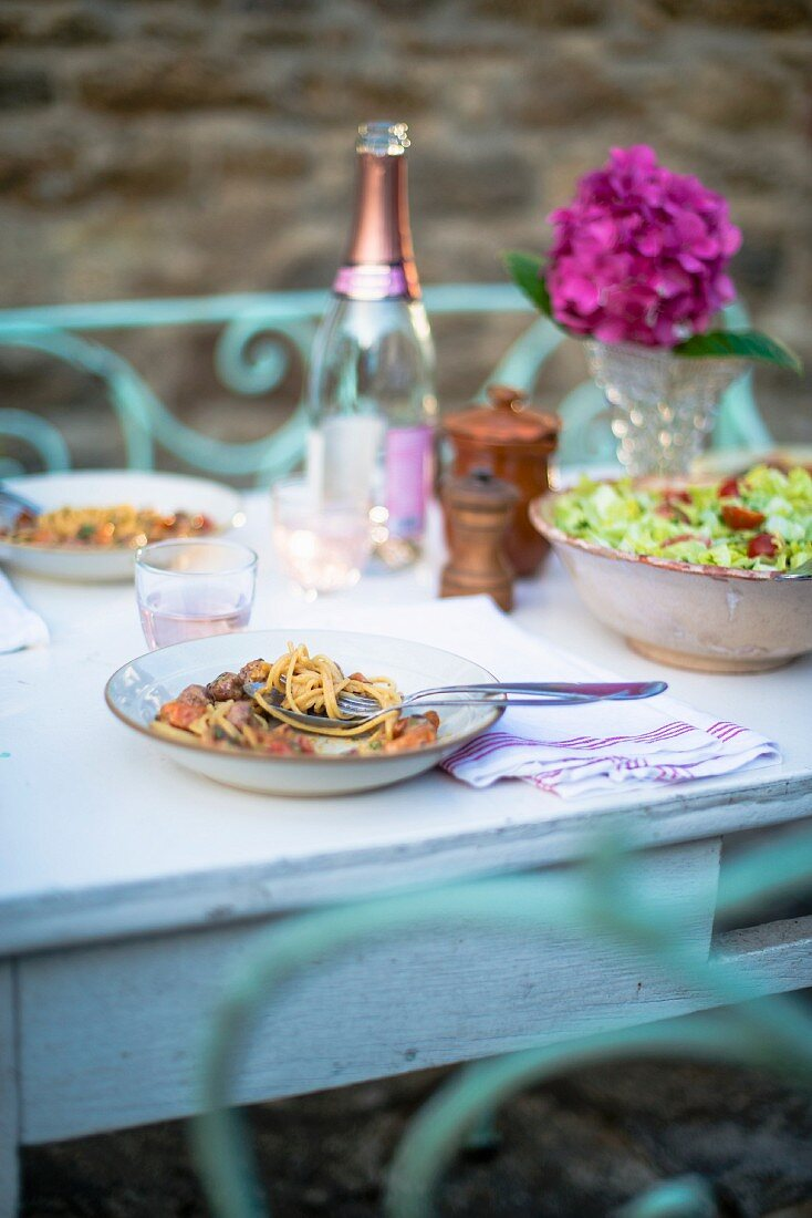Spaghetti with meatballs on plates and a bowl of green salad on a white terrace table