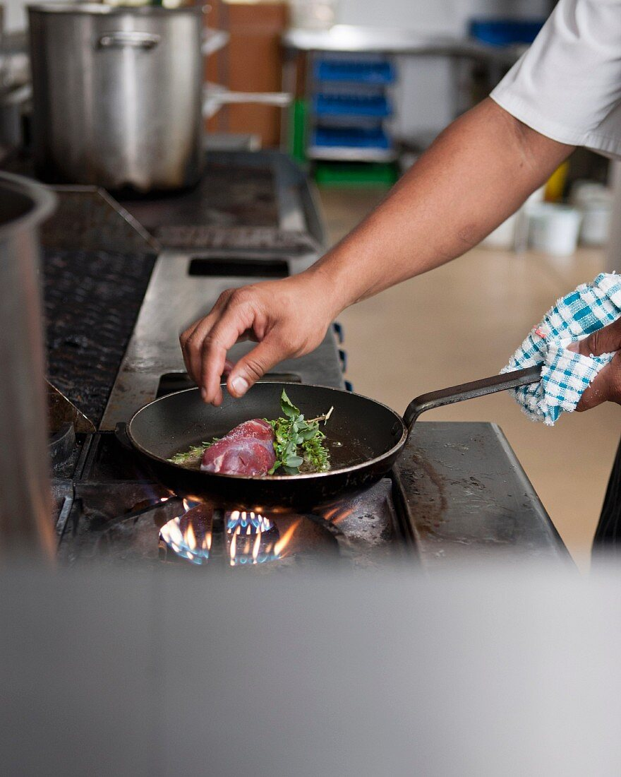 A chef frying lamb with wild herbs