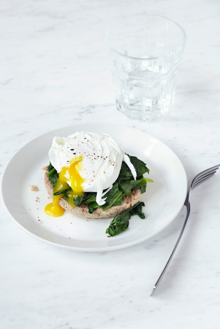 A poached egg with a soft yolk with spinach on an English muffin