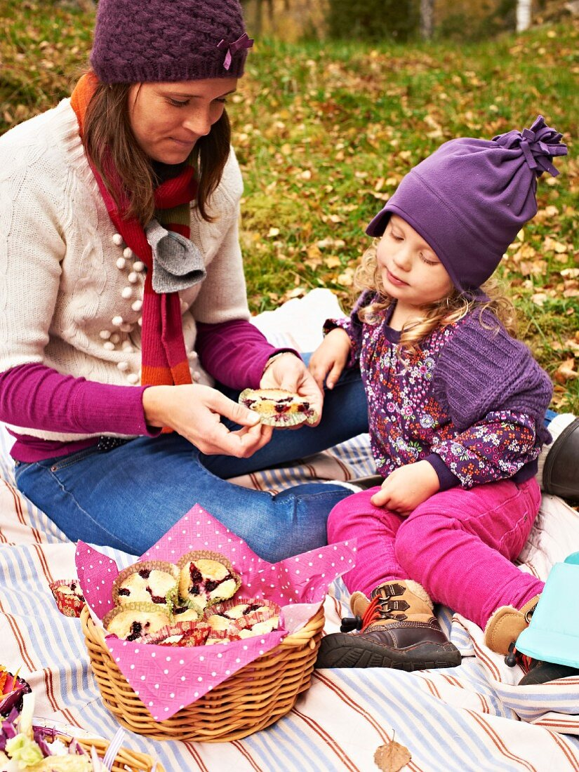 Autumn picnic: a mother and daughter eating blackberry muffins