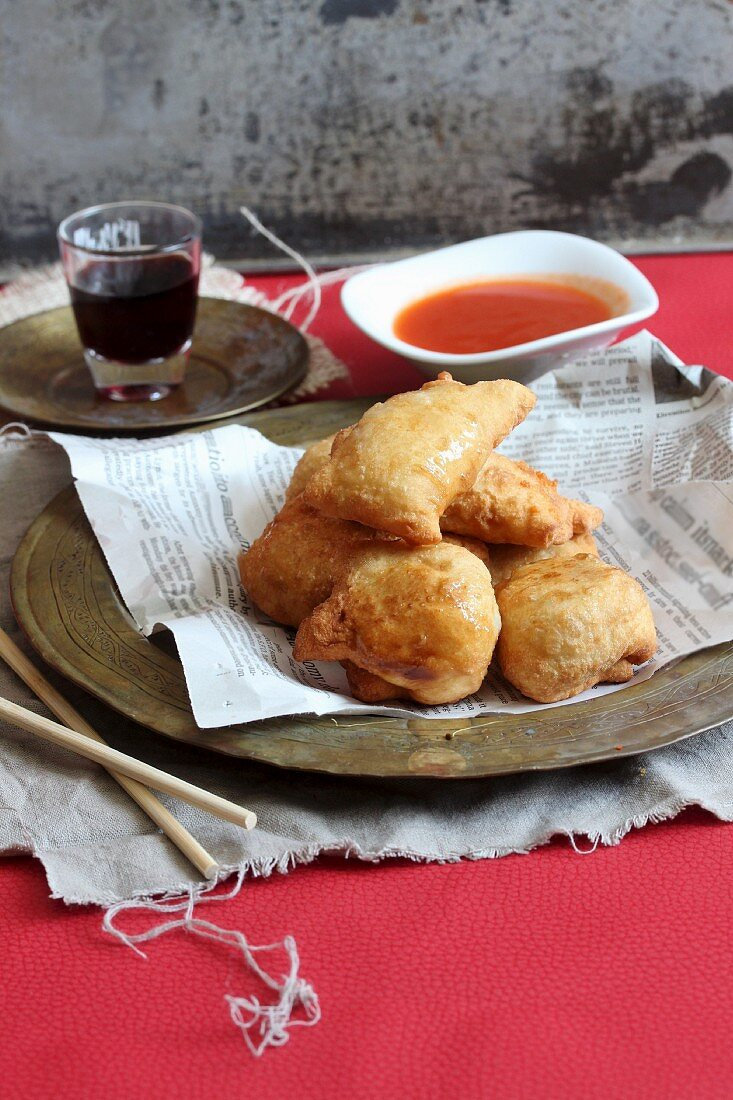 Chinese dumplings on a piece of newspaper with a dip