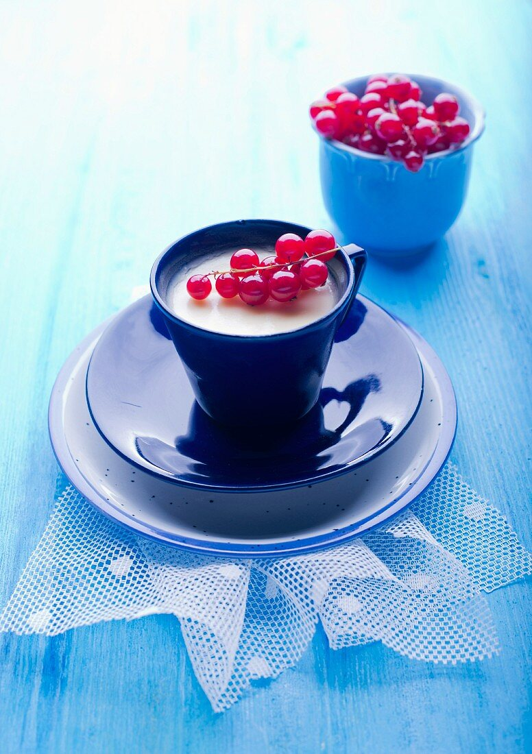 White chocolate mousse in a cup with redcurrants