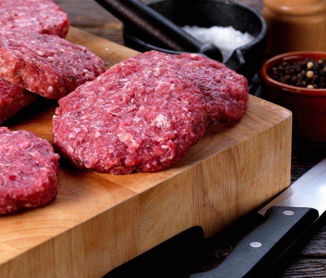 Raw wild boar burgers on a chopping board