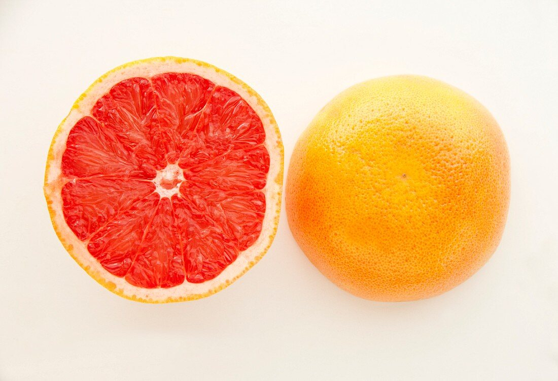 A halved pink grapefruit on a white surface