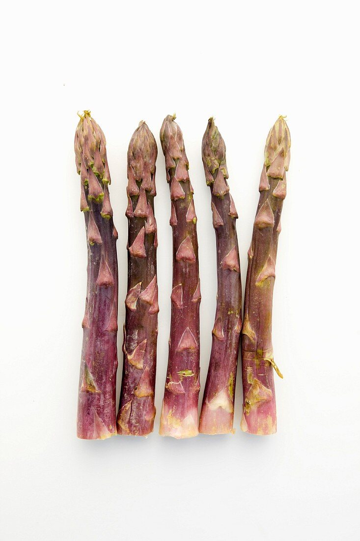 Five spears of purple asparagus on a white surface