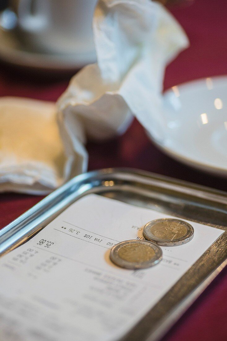 A bill and money on a tray in a restaurant